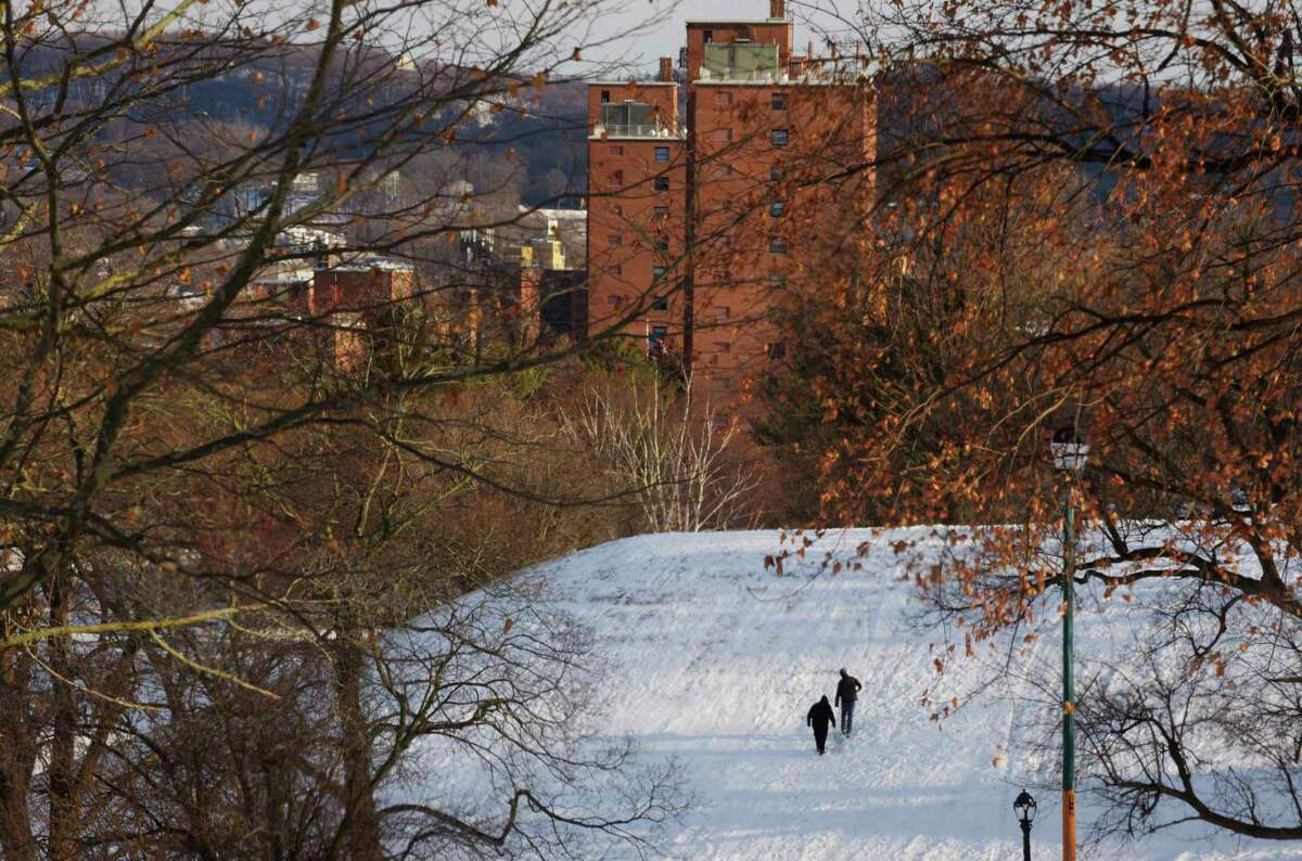 Two people make their way up a snow covered hill in Lincoln Park on Tuesday, Dec. 26, 2017, in Albany, N.Y. (Paul Buckowski / Times Union)