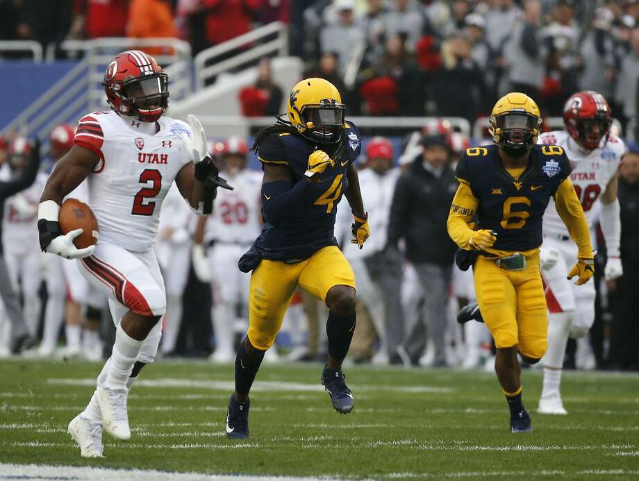 Utah's Zack Moss outraces West Virginia players for a 58-yard touchdown in the first quarter of the Heart of Dallas Bowl. Photo: Rose Baca, Associated Press