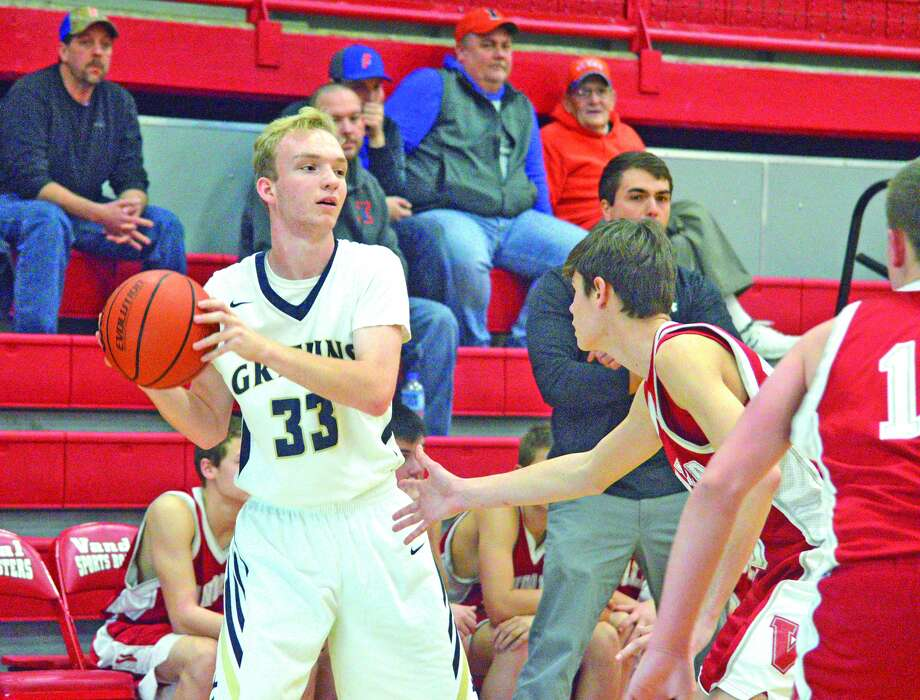 Father McGivney sophomore Zach Brasel, left, is guarded by a Vandalia junior varsity defender during Tuesday's second game of pool play at the Vandalia Holiday Tournament.