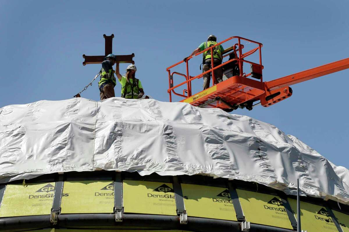 FILE- In this Aug. 10, 2017 file photo, construction workers adjust a temporary cross on the St. Nicholas National Shrine in New York. Work on the Greek Orthodox church destroyed in the Sept. 11 attacks next to the World Trade Center memorial plaza has been temporarily suspended by the construction company. It comes amid financial difficulties and questions over how funds have been managed. (AP Photo/Mark Lennihan, File)
