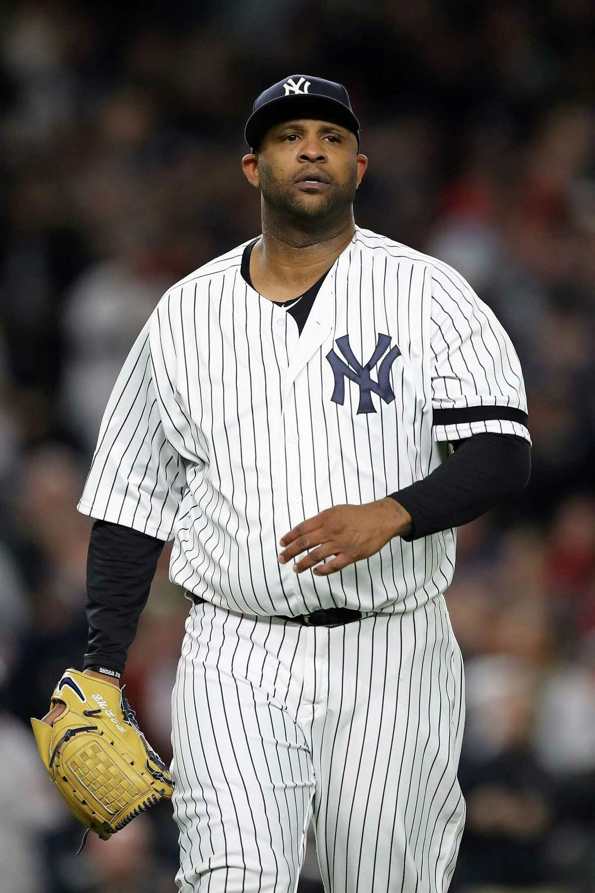NEW YORK, NY - OCTOBER 16: CC Sabathia #52 of the New York Yankees walks back to the dugout after a strikeout to end the top of the second inning against the Houston Astros in Game Three of the American League Championship Series at Yankee Stadium on October 16, 2017 in the Bronx borough of New York City. (Photo by Elsa/Getty Images) ORG XMIT: 775058091