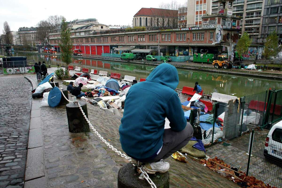 Migrants sit by a makeshift camp in Paris, Thursday, Dec. 21, 2017. The French government is scrambling to meet President Emmanuel Macron?'s deadline to get migrants off France?'s streets by year?'s end. (AP Photo/Thibault Camus)