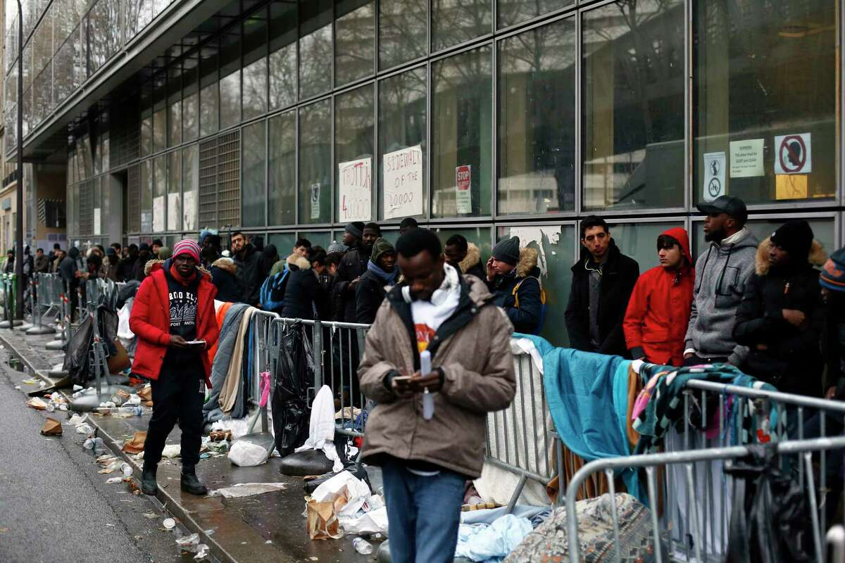 Migrants queue outside a facility to apply for asylum, in Paris, Thursday, Dec. 21, 2017. The French government is scrambling to meet President Emmanuel Macron?'s deadline to get migrants off France?'s streets by year?'s end. (AP Photo/Thibault Camus)