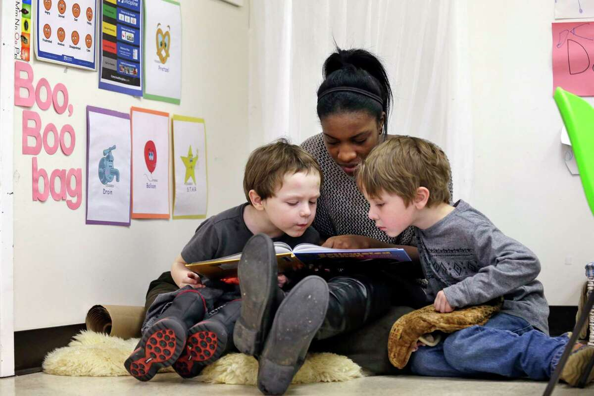 ** HOLD FOR SALLY HO STORY ** In this photo taken Feb. 12, 2016, assistant teacher D'onna Hartman, reads to Frederick Frenious, left, and Gus Saunders at the Creative Kids Learning Center, a school that focuses on pre-kindergarten for 4- and 5-year-olds, in Seattle. Hartman used the