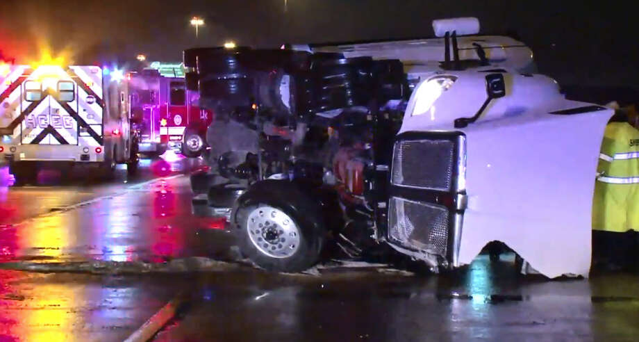 An 18-wheeler blocks traffic early Wednesday morning after jackknifing and flipping over onto its side. According to officials, the driver was attempting to avoid crashing into an abandoned, disabled vehicle left in the roadway. Photo: Metro Video
