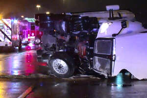 An 18-wheeler blocks traffic early Wednesday morning after jackknifing and flipping over onto its side. According to officials, the driver was attempting to avoid crashing into an abandoned, disabled vehicle left in the roadway.