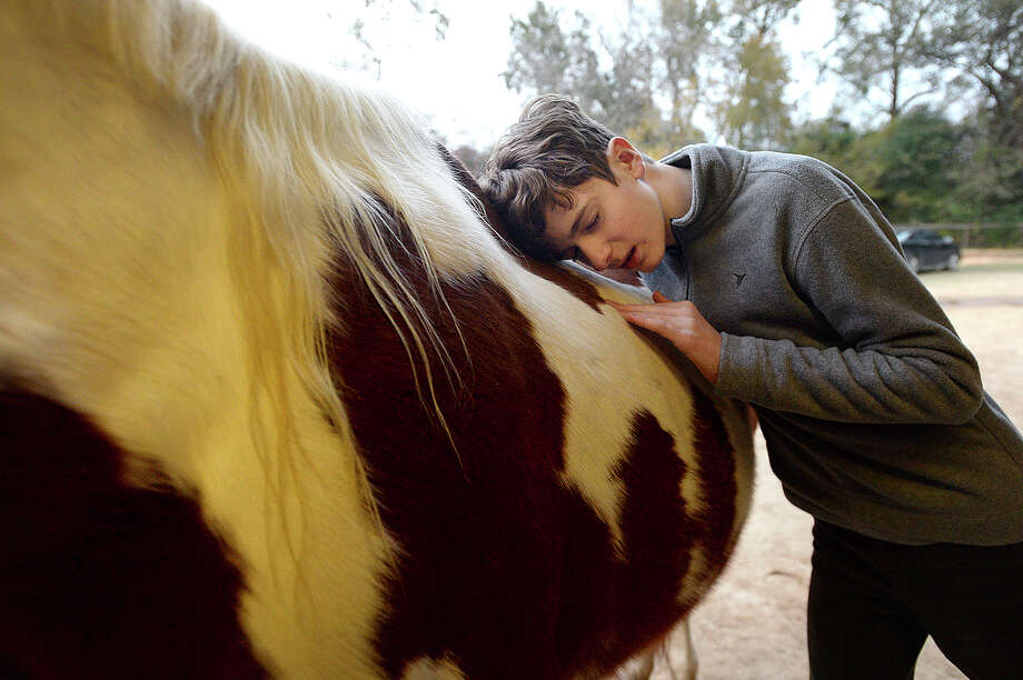 Parker Jackson, 14, of Bridge City hugs his therapy horse Patches after his riding session at Stable - Spirit Thursday, Dec. 14. Parker, who is autistic and deals with a commonly associated sensory processing disorder, has been taking weekly therapeutic riding sessions for about a year. Photo taken Thursday, December 14, 2017 Kim Brent/The Enterprise Photo: Kim Brent / BEN