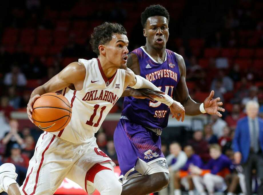 Oklahoma guard Trae Young (11) drives past Northwestern State forward Brandon Hutton, right, during a Dec. 19, 2017 game in Norman, Okla. Photo: Sue Ogrocki /AP Photo