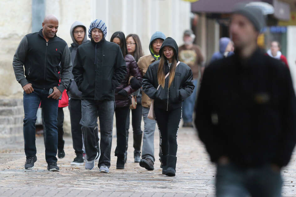 Pedestrians in front of the Alamo are bundled up for chilly temperatures Wednesday December 27, 2017.