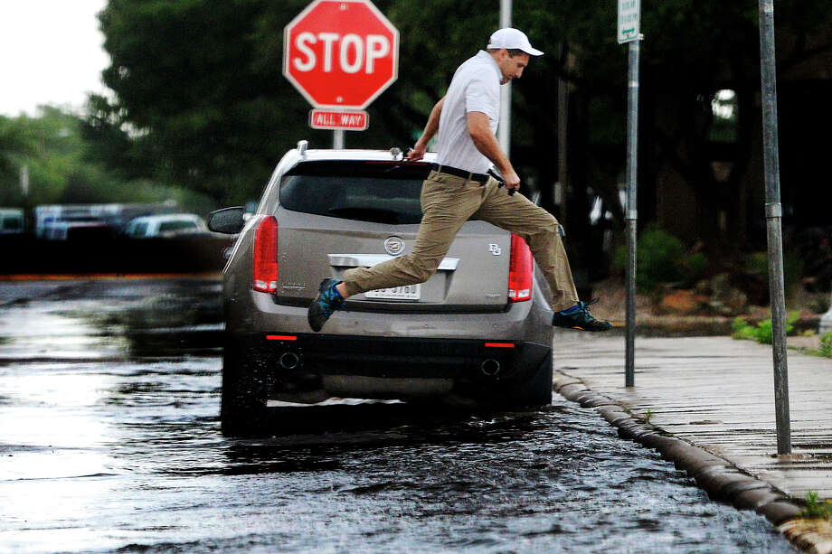 Kris Karnes takes a running leap to clear flooding along Missouri Ave. during a rainstorm Wednesday, May 31, 2017. James Durbin/Reporter-Telegram Photo: James Durbin