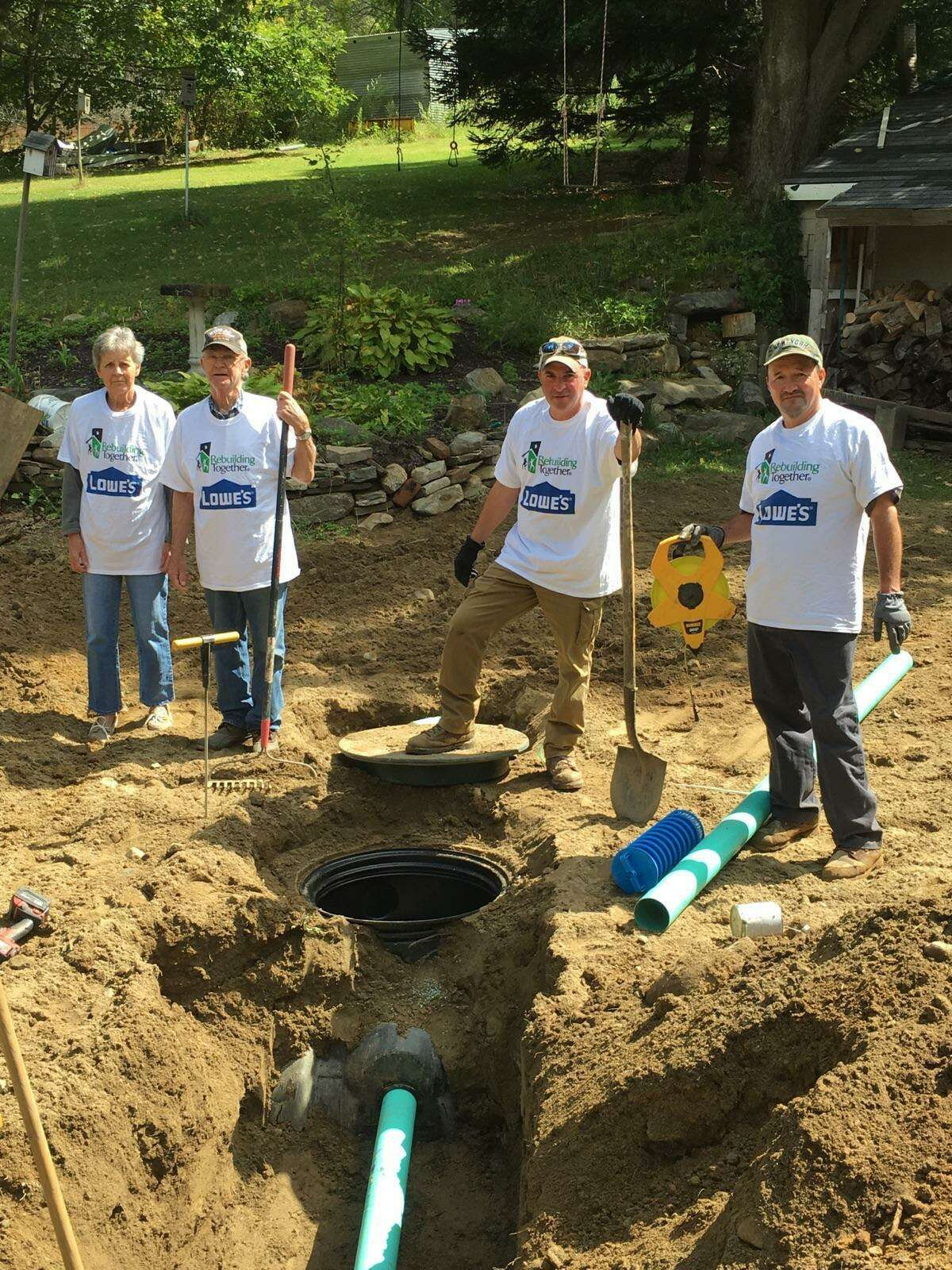 Lowe's Home Improvement recently partnered with Rebuilding Together Litchfield County and New Milford Septic to replace a septic system for a New Preston veteran. Volunteers are shown above working on the project.
