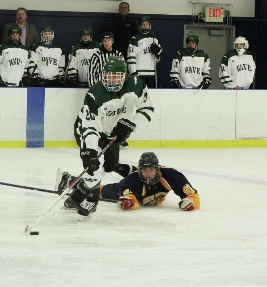 Senior Ben Paquin checks an East Haven opponent to get the puck. Photo: Courtesy Of Katie Alzapiedi / The News-Times Contributed