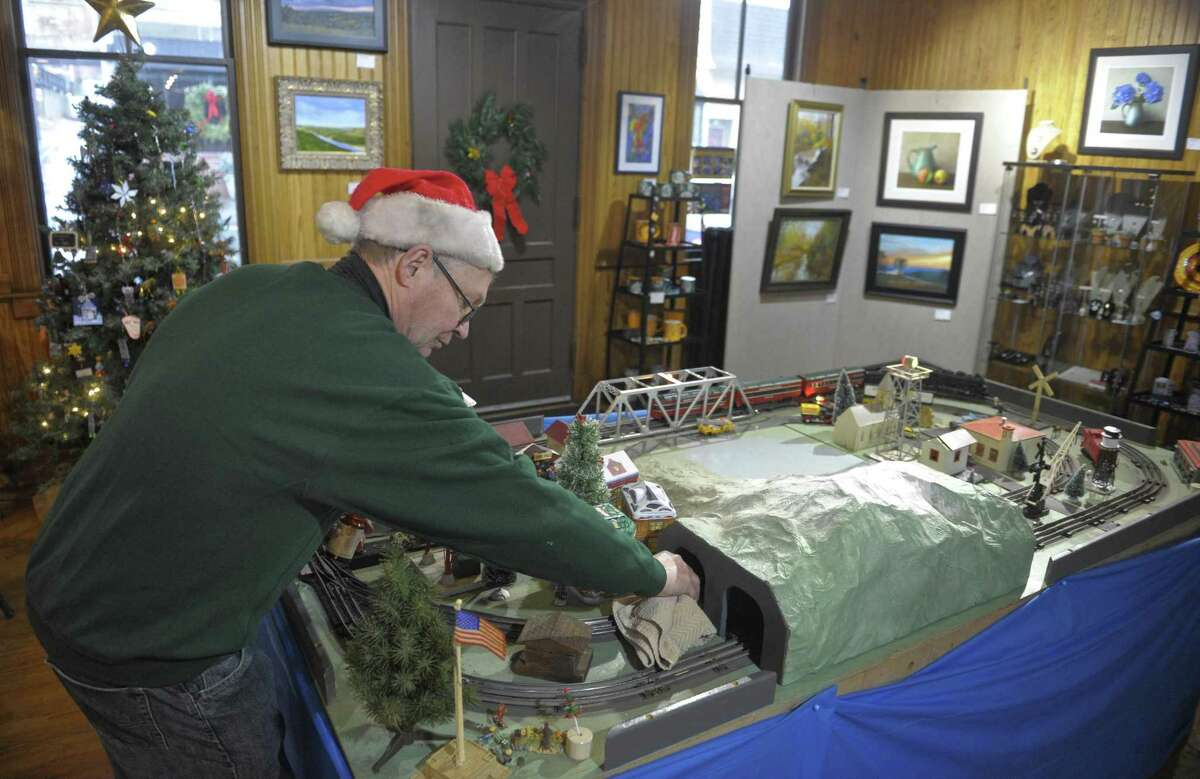 Above, train enthusiast Jim Hamill, of New Milford, cleans tracks at the annual holiday train display at Gallery 25. Below, Cameron Connor, 2, of New Milford, takes in the event.
