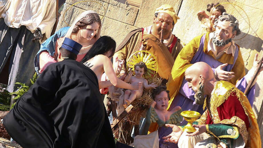 A topless woman from an activist group tried to escape with a baby Jesus statue off of a nativity scene at the Vatican on Christmas Day.