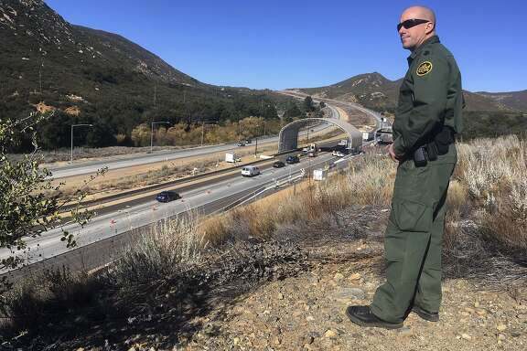 CORRECTS PHOTOGRAPHER NAME TO ELLIOT FROM ELLIOTT - In this Thursday, Dec. 14, 2017 photo, Border Patrol agent Troy Hunt looks over California's Pine Valley checkpoint, on the main route from Arizona to San Diego. California legalizes marijuana for recreational use Jan. 1 but that won't stop federal agents from seizing small amounts on busy freeways and backcountry highways. Possession will still be prohibited at eight Border Patrol checkpoints in California, a daily demonstration of state and federal law colliding. (AP Photo/Elliot Spagat)
