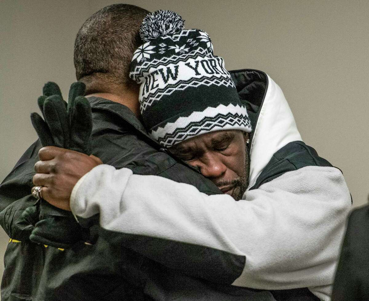 Charles Mayben Jr., right, a basketball coach for one of the murdered children, is comforted by clergy member Rev. Charles Burkes after a press briefing on Wednesday, Dec 27, 2017, at City Hall regarding the quadruple murder that was discovered Tuesday in Troy, N.Y. (Skip Dickstein/ Times Union)
