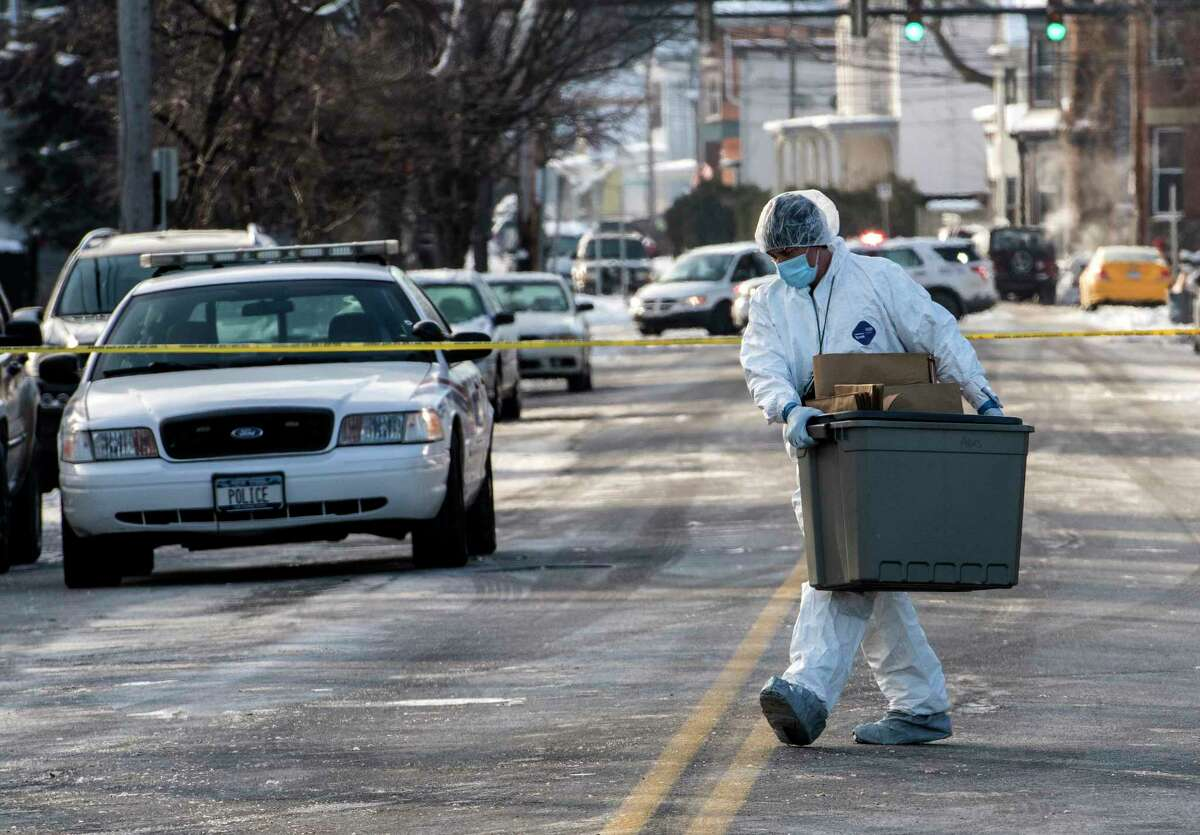Members of the NYSP Troop G Forensics Unit carry evidence containers to the building on Second Ave. where a quadruple murder was discovered Tuesday, shown on Wednesday, Dec 27, 2017, in Troy, N.Y. (Skip Dickstein/ Times Union)