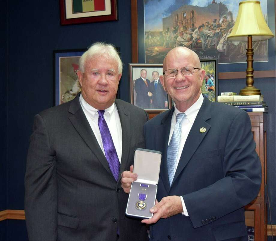 Retired Navy Capt. Michael Penn, a Vietnam veteran and former prisoner of war, receives a new Purple Heart medal from U.S. Rep. Ted Poe. Eleven of Penn's medals were replaced after being damaged when Hurricane Harvey's floodwaters engulfed his Kingwood home. Photo: Courtesy Of Ted Poe Facebook Page