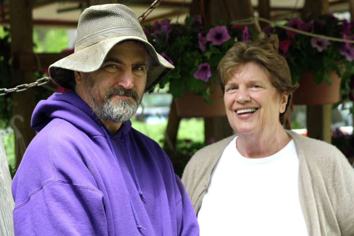 Ed Gazy and loyal customer Fran Schneidau, who is a big fan of Gazy's plants, stand in front of his booth in 2011. Schneidau, whose voice was instantly recognizable to news radio listeners throughout the state, has died at the age of 79, according to WCBS 880.