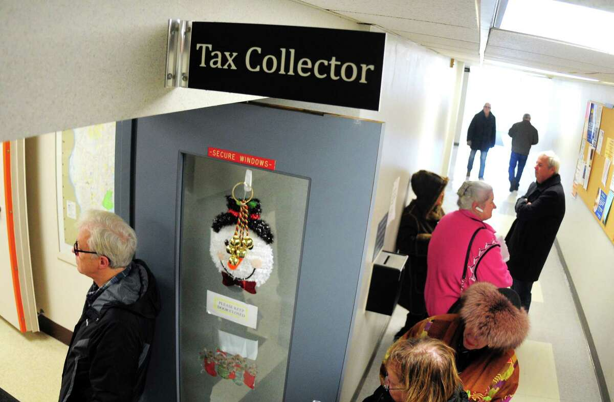 Milford residents wait in line to pay their taxes at the Parsons Goverment Complex in Milford, Conn., on Wednesday, Dec. 27, 2017. The new federal tax overhaul that curbs how much homeowners can deduct for property taxes has many residents inquiring whether they can prepay their future taxes to avoid the hit.