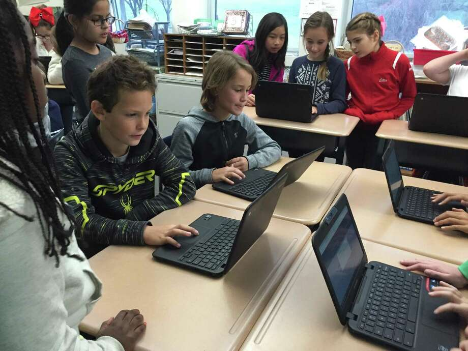 Students at Wilton Public Schools access their devices in class. Photo: Contributed Photo /