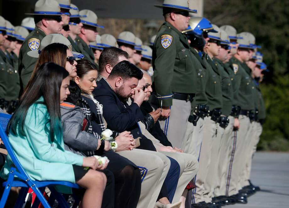 Family members of California Highway Patrol Officer Andrew Camilleri, including daughter Elizabeth (left), 12, and wife Rosanna (second from left), mourn at a bell toll tribute ceremony at the CHP Academy. Photo: Paul Chinn, The Chronicle