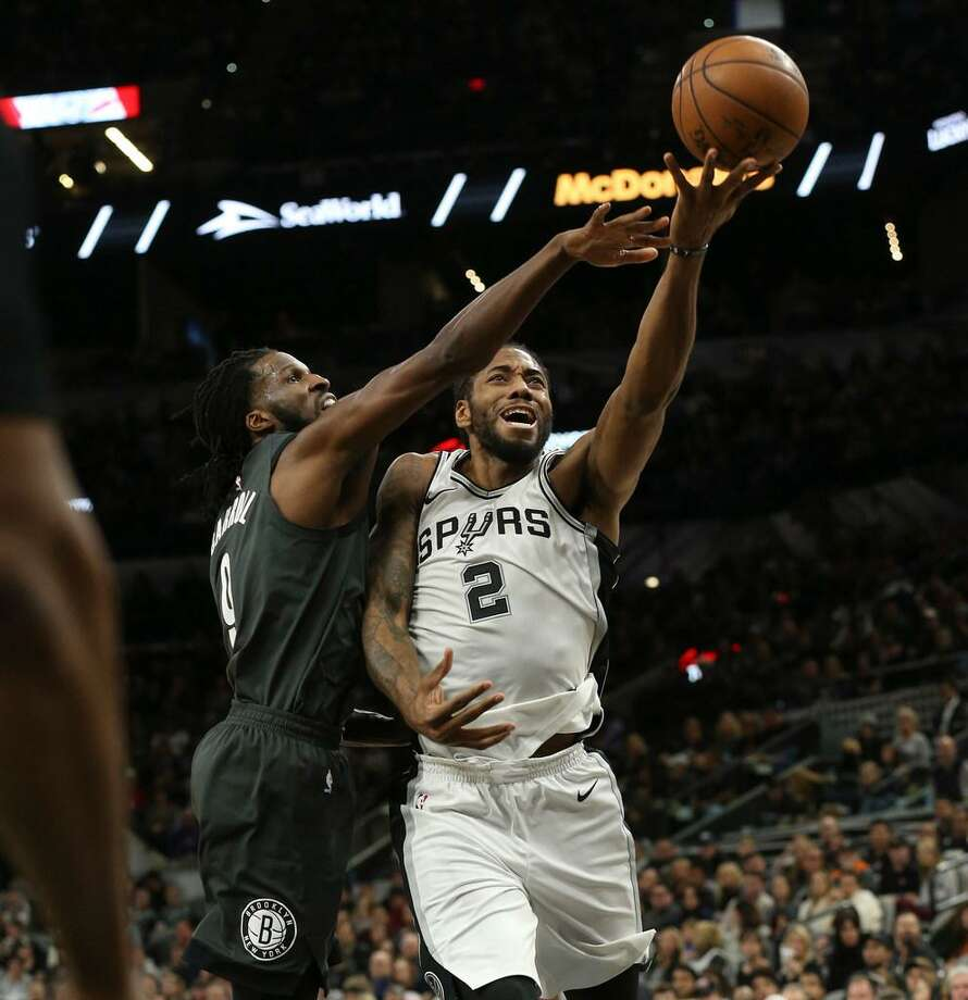 Spurs forward Kawhi Leonard gets fouled by Brooklyn's DeMarre Carroll as he goes up for a shot at the AT&T Center on Dec. 26, 2017. Photo: Kin Man Hui /San Antonio Express-News