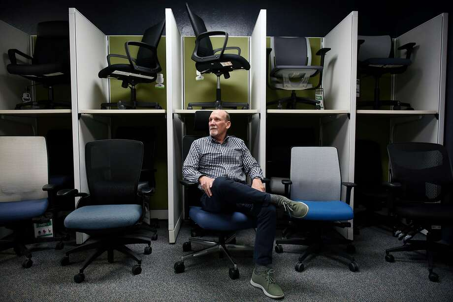 Michael Hannigan, president of Give Something Back, which sells wholesale office supplies, sits among chairs sold by his Oak land company. He avoids asking job candidates about criminal history and supports a new state law that limits the practice. Photo: Michael Short, Special To The Chronicle