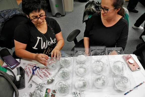 Laurie Valdez finishes up prepping commemorative Christmas ornaments with Corina Cardenas during a holiday party at Silicon Valley De-Bug in San Jose, Calif., on Wednesday, December 20, 2017. Valdez's partner, Antonio Guzman Lopez, was shot and killed by San Jose State Police in 2014, and Cardenas's father Rudy Cardenas was also killed by police. Silicon Valley De Bug has received a grant from the Colin Kaepernick Foundation to help provide a healing retreat for families of men killed by police.