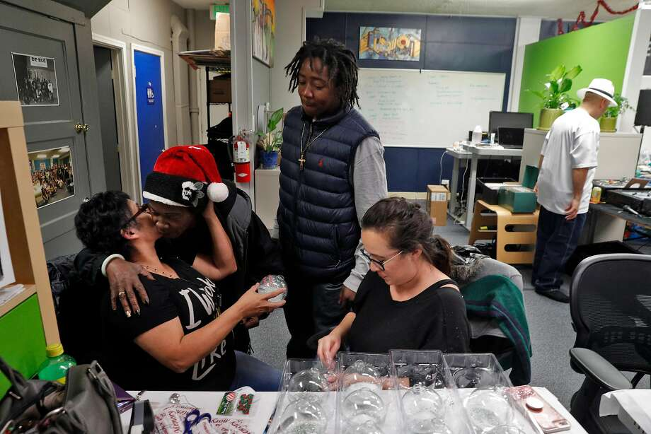 Laurie Valdez (seated left) gets a hug and kiss from Debora Sires as she finishes up prepping commemorative Christmas ornaments with Corina Cardenas during a holiday party at Silicon Valley De-Bug in San Jose last week. Valdez's partner, Antonio Guzman Lopez, was shot and killed by San Jose State police in 2014, and Cardenas' father, Rudy Cardenas, was also killed by police. Silicon Valley De Bug has received a grant from the Colin Kaepernick Foundation to help provide a healing retreat for families of men killed by police. Photo: Carlos Avila Gonzalez, The Chronicle