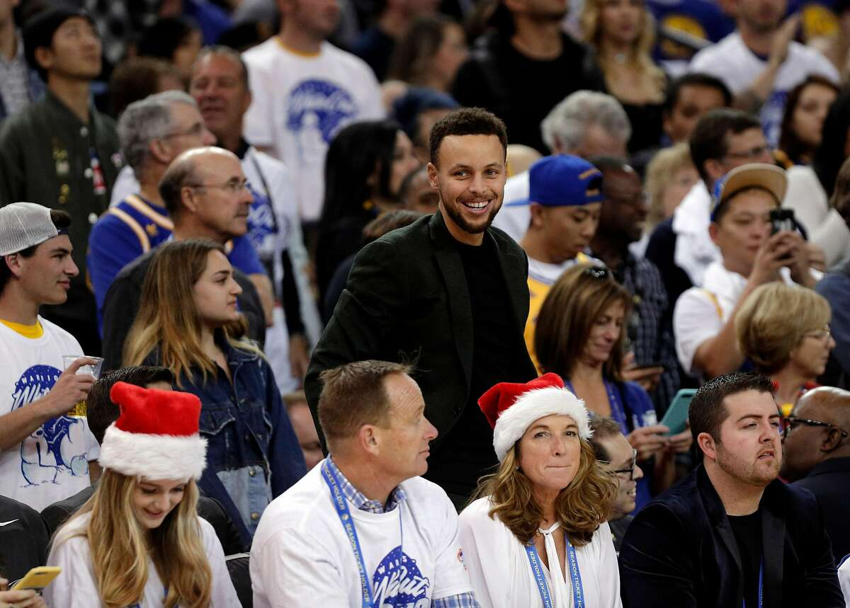 Stephen Curry (30) laughs from behind the bench in the second half as the Golden State Warriors played the Cleveland Cavaliers at Oracle Arena in Oakland, Calif., on Monday, December 25, 2017.