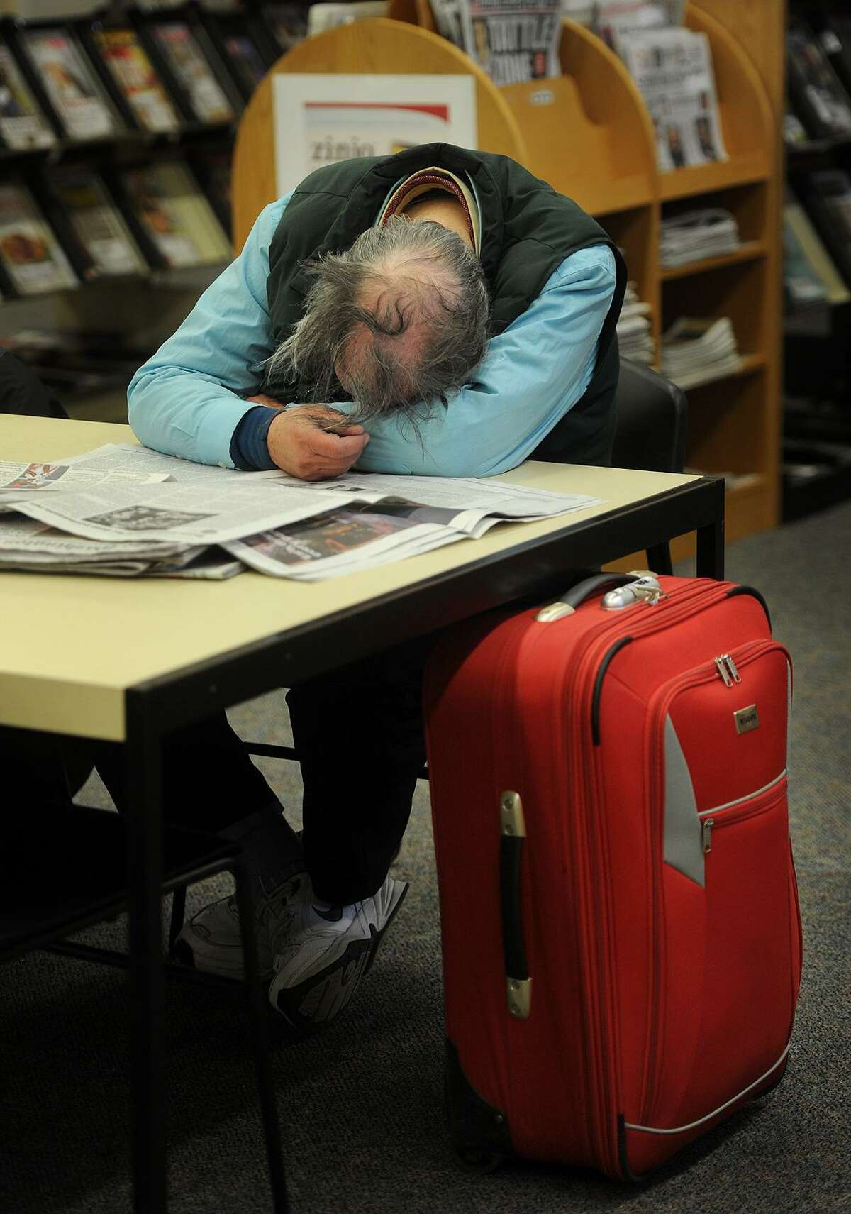 A man sleeps next to a suitcase of his belongings at the Bridgeport Public Library on Wednesday.