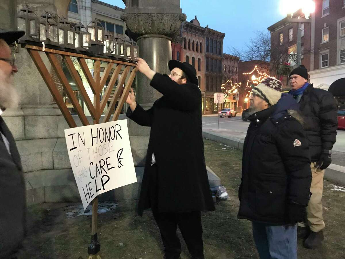 Troy Chabad honored some of the dedicated people helping their community with the lighting of a large menorah in Troy?s Monument Square last Sunday. Mayor Patrick Madden made the first lighting, followed by Milton Architzel, center, a teacher for 47 years in Troy, watching his candle being placed by Rabbi Shleima Morrison. Next were military veterans Samuel Rosenfeld, on right, and Allen Feldman; and RPI student Caleb Gladstone. (Leible Morrison)