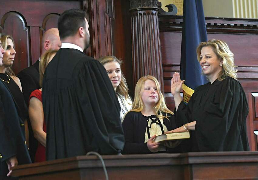 Judge Andrew Ceresia, left, delivers the oath of office to Democrat Jennifer Sober of Schodack as Rensselaer County Court judge in the Rensselaer County Court House on Wednesday, Dec. 27, 2017 in Troy, N.Y. Sober's daughter Claire, 11, holds the holy bible. (Lori Van Buren / Times Union)