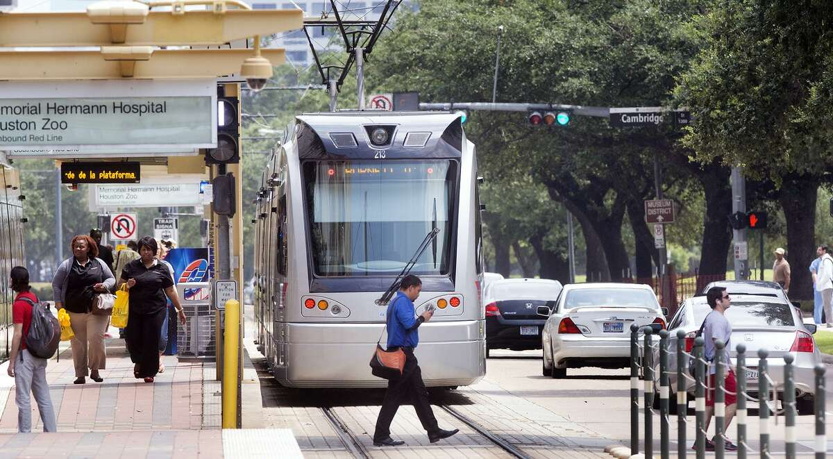 A METRO rail makes its way along the track as a group of pedestrians cross Fannin Street in the Medical Center, Thursday, July 24, 2014, in Houston. (Cody Duty / Houston Chronicle)