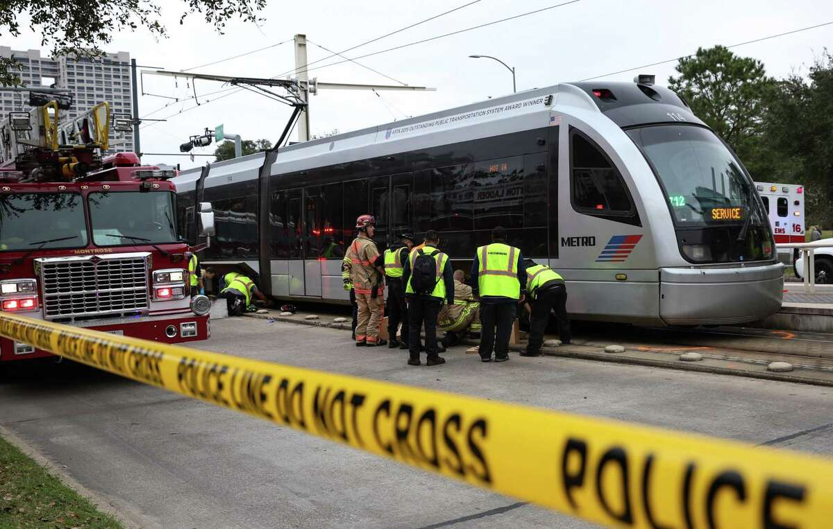 A Metro train is examined after it struck and killed a bicyclist in February. Most incidents involve vehicles, and many of those are from vehicles making illegal left turns into the rail space.