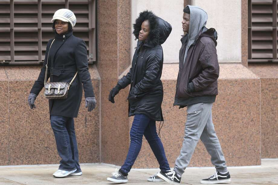 Pedestrians on East Commerce street are bundled up for chilly temperatures Wednesday December 27, 2017. Temperatures are expected to drop to the 40s on April 7, 2018. Photo: John Davenport, STAFF / San Antonio Express-News / ©John Davenport/San Antonio Express-News