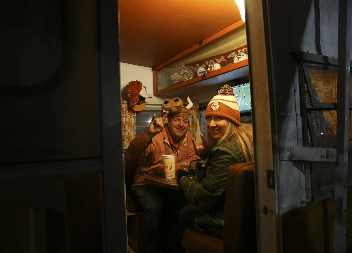 Texas fans Chris Slahetka and Karn Flowers enjoy themselves in a Texas-themed camper while tailgating before the 2017 Academy Sports + Outdoors Texas Bowl at NRG Stadium on Wednesday, Dec. 27, 2017, in Houston. ( Yi-Chin Lee / Houston Chronicle )