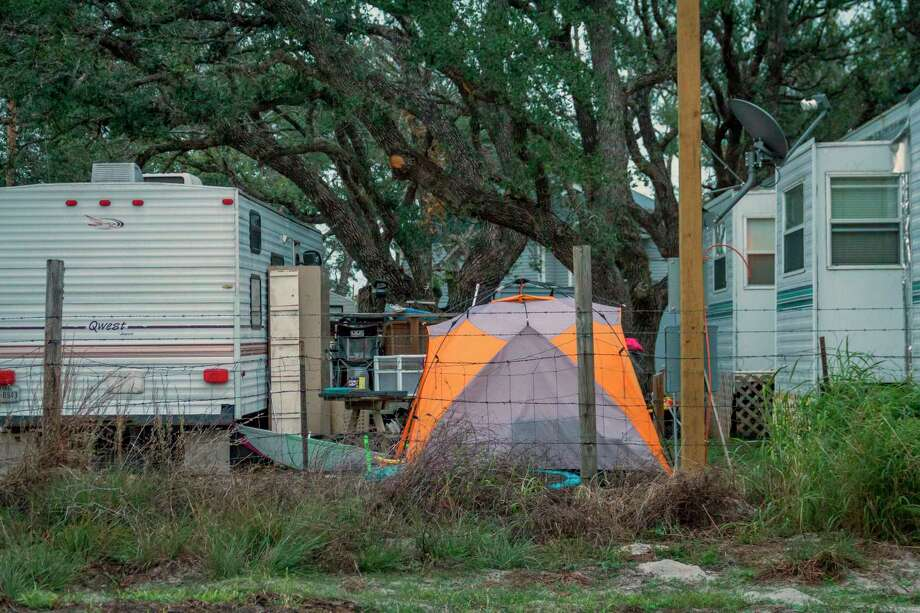 In this Dec. 15, 2017 photo provided by Kim Porter, shows people living in tents and trailers in Rockport, Texas. The federal government typically spends up to $150,000 apiece _ not counting utilities, maintenance or labor _ on the trailers it leases to disaster victims, then auctions them at cut-rate prices after 18 months of use or the first sign of minor damage. Officials have continued the practice even amid a temporary housing shortage in Texas, where almost 8,000 applicants are still awaiting federal support nearly four months after Hurricane Harvey landed in the Gulf Coast. (Kim Porter via AP) Photo: Kim Porter, HONS / Kim Porter