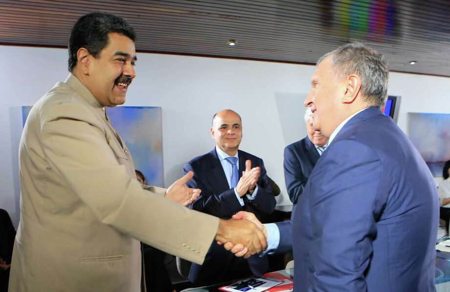"""This handout photo from the Venezuelan Presidency shows Venezuelan President Nicolas Maduro (L) greeting the head of the Russian state-owned oil giant Rosneft, Igor Sechin, during a meeting in Caracas on December 16, 2017. / AFP PHOTO / Venezuelan Presidency / HO / RESTRICTED TO EDITORIAL USE-MANDATORY CREDIT """"AFP PHOTO/VENEZUELAN PRESIDENCY/HO"""" NO MARKETING NO ADVERTISING CAMPAIGNS-DISTRIBUTED AS A SERVICE TO CLIENTS-GETTY OUTHO/AFP/Getty Images Photo: HO, Contributor / AFP or licensors"""