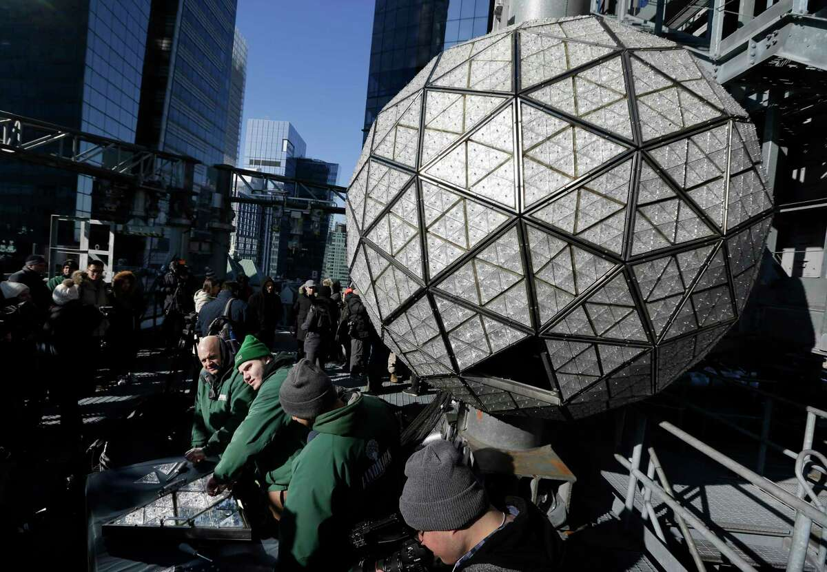 Workers prepare to install the last panels on the New Year's Eve ball above Times Square, New York, Wednesday, Dec. 27, 2017. The 12-foot diameter ball carries over 2600 Waterford crystals and is lit by more than 32,000 LEDs. (AP Photo/Seth Wenig)