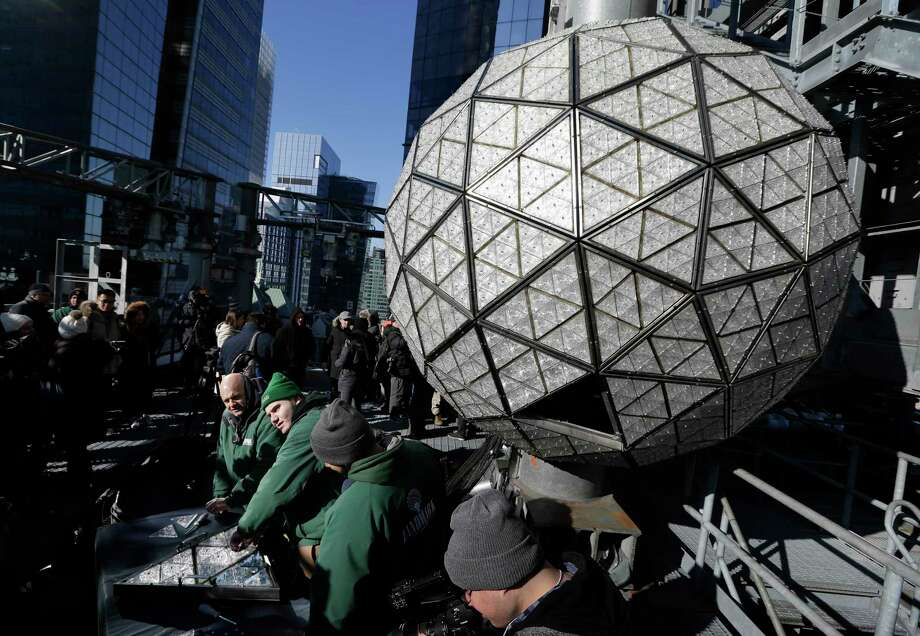 Workers prepare to install the last panels on the New Year's Eve ball above Times Square, New York, Wednesday, Dec. 27, 2017. The 12-foot diameter ball carries over 2600 Waterford crystals and is lit by more than 32,000 LEDs. (AP Photo/Seth Wenig) Photo: Seth Wenig / Copyright 2017 The Associated Press. All rights reserved.