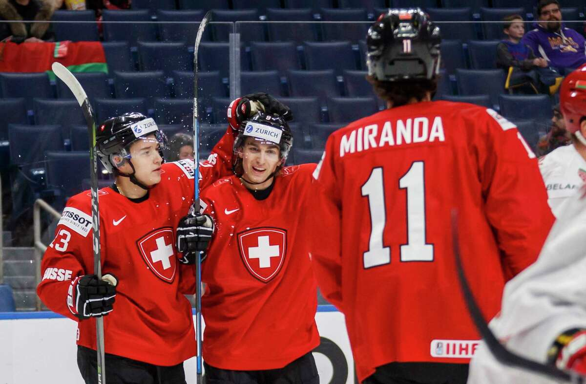 Switzerland's Nicolas Muller, center, celebrates his goal with teammates Philipp Kurashev, left, and Marco Miranda against Belarus during the first period of IIHF World Junior Championship preliminary round hockey action in Buffalo, N.Y. Wednesday, Dec. 27, 2017. (Mark Blinch/The Canadian Press via AP)