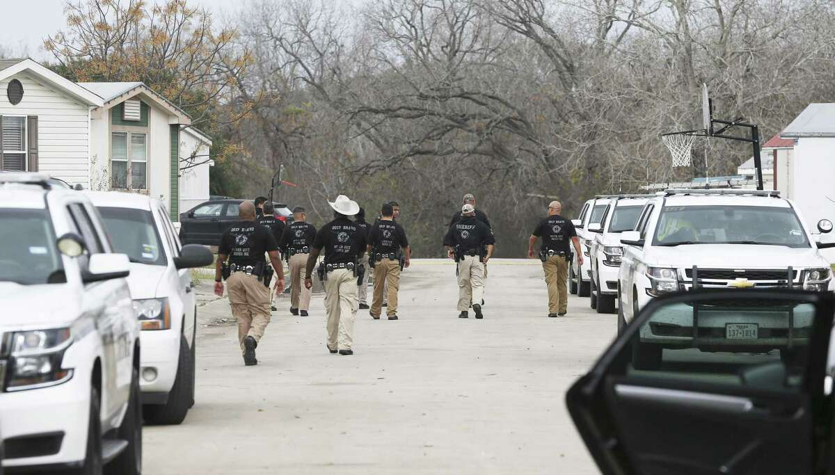 Law enforcement officials walk the area and investigate after Bexar County sheriff's deputies opened fire at a wanted felon in 100 block of Peach Lane in Schertz last week. The wanted woman, who was unarmed, was killed by the gunfire, as was a 6-year-old boy in his home.