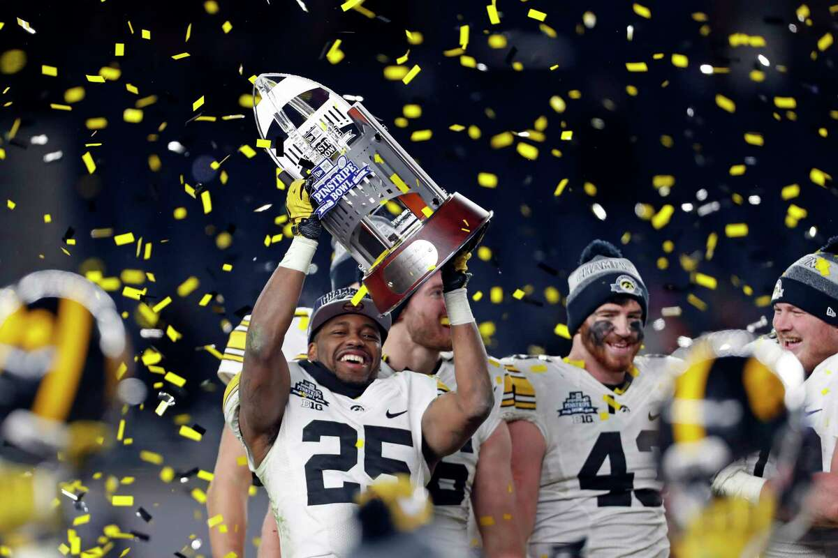 NEW YORK, NY - DECEMBER 27: Akrum Wadley #25 of the Iowa Hawkeyes holds up the George M. Steinbrenner III Trophy after defeating the Boston College Eagles in the New Era Pinstripe Bowl at Yankee Stadium on December 27, 2017 in the Bronx borough of New York City. The Iowa Hawkeyes won 27-20. (Photo by Adam Hunger/Getty Images)