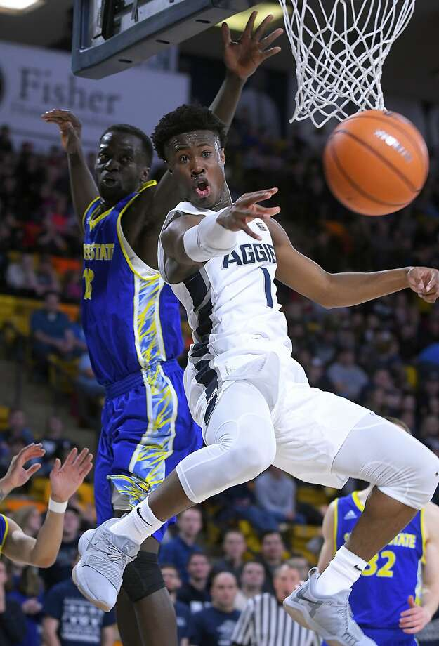 Utah State guard Koby McEwen makes a pass with San Jose State's Oumar Barry in the background. McEwen had 24 points and five assists as the Aggies prevailed. Photo: Eli Lucero, Associated Press