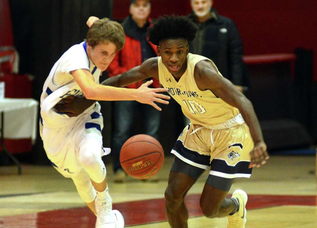 Notre Dame of Fairfield's Woodley Monnexant, right, tries to reach the ball first after stealing the ball away from Fairfield Ludlowe's Jeffrey Meyers during Fairfield Prep Holiday Classic basketball action in Fairfield, Conn., on Wednesday Dec. 27, 2017.