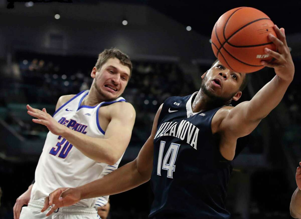Villanova's Omari Spellman (14) reaches for a rebound against DePaul's Peter Ryckbosch during the first half of an NCAA college basketball game Wednesday, Dec. 27, 2017, in Chicago. (AP Photo/Jim Young)