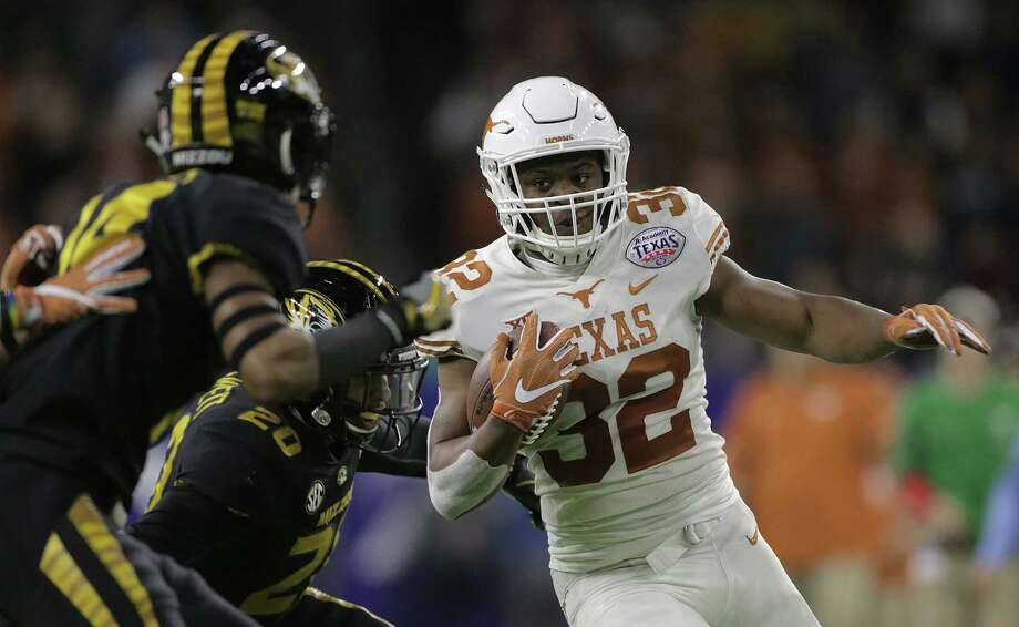 Texas Longhorns running back Daniel Young (32) runs for extra yards against Missouri Tigers in the first quarter of  the Academy Sports & Outdoors Texas Bowl at NRG Stadium on Wednesday, Dec. 27, 2017, in Houston. ( Elizabeth Conley / Houston Chronicle ) Photo: Elizabeth Conley, Chronicle / © 2017 Houston Chronicle