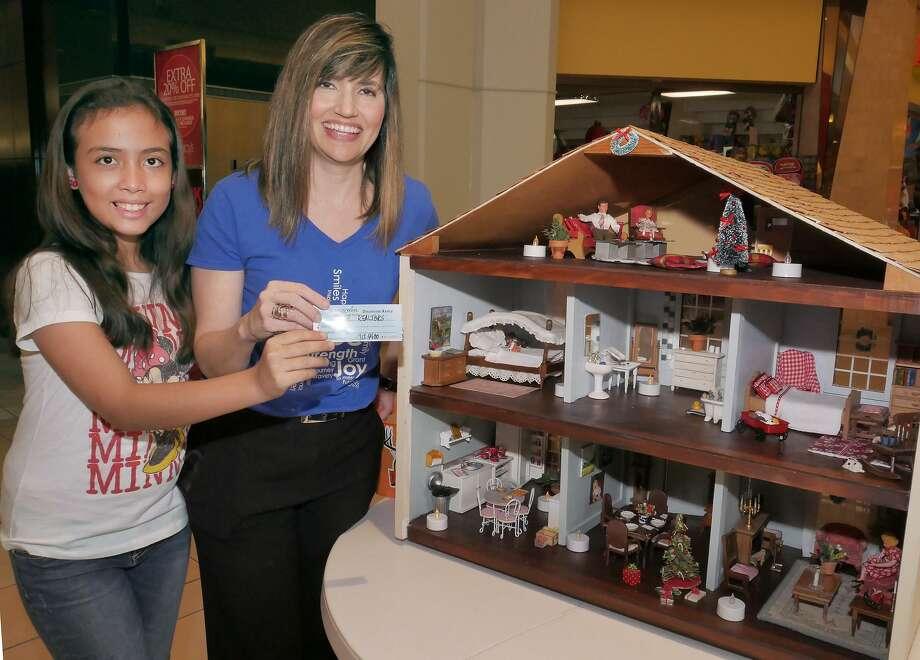 Krychel Elías, una niña Wish Child y Elizabeth O'Conor sostienen el boleto ganador de la casa de muñecas que perteneció a O'Conor en su niñez y que rifó en noviembre. Photo: Cuate Santos /Laredo Morning Times / Laredo Morning Times
